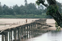 Exit ramp on a bridge to nowhere. As a man fishes underneath, a woman crosses a long ago bombed out bridge in northern Vietnam, reinforced and made usable the Stock Image