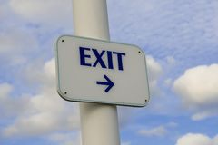 Exit sign. Post pointing to the right against blue sky Stock Images