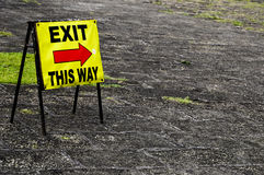 Exit sign. A old yellow exit sign pointing the way out Stock Photography