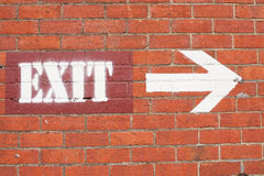 Exit sign and arrow. White exit sign and arrow painted on red brick wall Stock Image