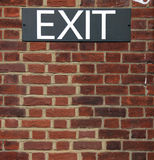 Exit sign on brick wall. A black and white exit sign put up on a red brick wall Stock Images