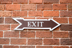 Exit sign on brick wall. Arrow exit sign on brick wall Royalty Free Stock Photography