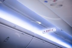 Exit sign in in the aircraft cabin. Exit sign in in the cabin above the overhead stowage of the aircraft Royalty Free Stock Photo