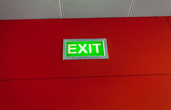 Exit sign glowing on red wall Stock Photography