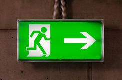 Exit sign. Green emergency exit sign on the concrete wall Royalty Free Stock Photo
