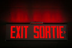 Exit Sign. Red exit sign in English and French reflecting on concrete ceiling Royalty Free Stock Photography