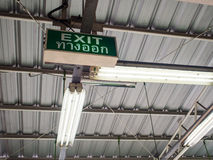 Exit sign with thai word means exit under old factory roof Stock Photo