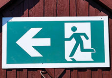 Exit sign on the wall of a building. Exit sign on the wall of a wooden building Stock Photo