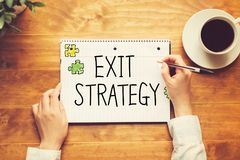Exit Strategy text with a person holding a pen stock photography