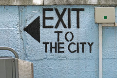 Exit. To the city sign with arrow at wall Royalty Free Stock Photo