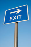 Exit this way. Exit sign silhouetted against a clear blue sky Stock Photo