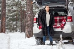 Exited adult Caucasian woman in unbutton fur coat stands full-length near own car. Walking in wintry forests. Copy space Royalty Free Stock Images