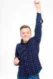 Exited cheerful successful man raised hand up gesturing victory Stock Photo