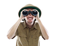 Exited explorer looking through binoculars. Young smiling man wearing pith helmet looking through binoculars, isolated on white Stock Image