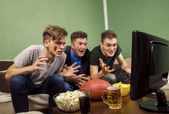 Exited family , father and sons watching football. Exited family , father and sons watching American football on television royalty free stock image