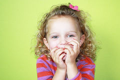 Exited girl. Happy little girl with hands in front of her mouth Royalty Free Stock Image
