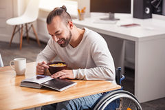Exited handicapped guy eating cereal in the morning Royalty Free Stock Images