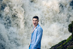 Exited happy man standing near water fall and looking at camera royalty free stock photography