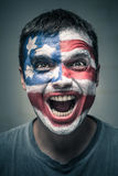 Exited man with US flag painted on face Stock Images