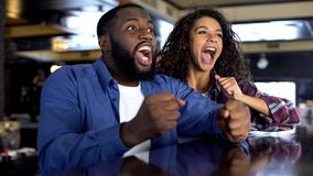 Exited multiethnic couple rooting for national team watching game, entertainment. Stock photo royalty free stock image