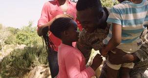 Exited returning soldier man meeting his wife and children