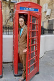 Exiting Phone Booth. A young well-dressed man exits an old telephone booth in Malta Stock Photography