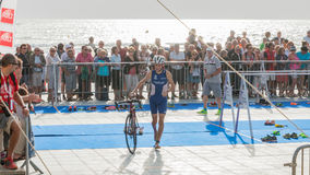 After exiting the water, athletes take their racing bike Royalty Free Stock Image