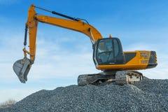 Exkavator on big pile of gravel Stock Photo