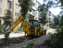 exkavator Straßenreparatur der Straße im Gartenarbeitskraft escavator Stockbilder