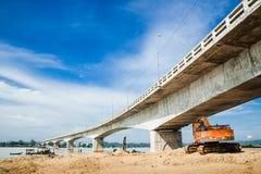 Exkavator unter einer Brücke stockfotos