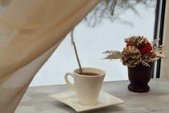 Exklusive Porzellanschale mit schwarzem scharfem aromatischem Kaffee und dekorativer Blumenstrauß im keramischen Vase auf einem h lizenzfreie stockbilder