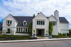 Exklusivt två-berättelse hus av vit tegelsten, med nätt landskap Arkivfoton