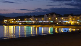 Exmouth beach at twilight. Lights sparkle in the sea on a beach in wintertime Exmouth devon UK #Exmouth Stock Photography