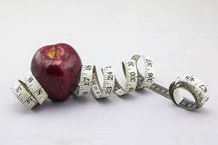Exotic Apple being surrounded by measure tape. It could be useful to promote weight loss and fitness campaign Royalty Free Stock Image
