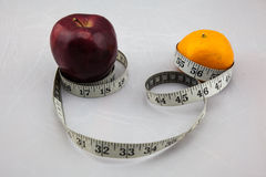 Exotic Apple and Orange being surrounded by measure tape. It could be useful to promote weight loss and fitness campaign Royalty Free Stock Photo