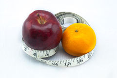 Exotic Apple and Orange being surrounded by measure tape. It could be useful to promote weight loss and fitness campaign Stock Photography