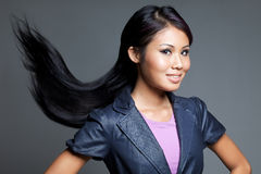 Exotic Asian woman with long, silky hair. Studio portrait of a beautiful Malay Chinese Peranankan woman with windswept hair glancing sideways Royalty Free Stock Photography