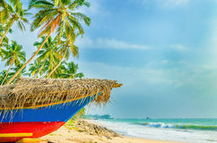 Exotic beach with colorful boat, tall palm trees Royalty Free Stock Images