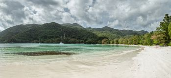 Exotic beach with white sand, azure water, green hills and red leaves on the tree. Port Launay, Seychelles Royalty Free Stock Photo