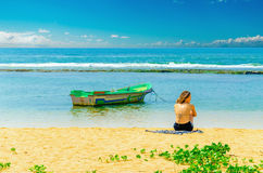 Exotic beach, young girl, fishing boat and water Royalty Free Stock Photo