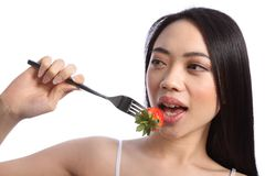 Exotic beautiful oriental girl eating strawberry Stock Photos