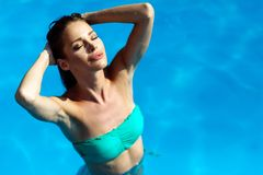 Exotic beautiful woman sunbathing and swimming. Exotic beautiful woman relaxing sunbathing and swimming in pool stock photos
