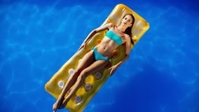 Exotic beautiful woman sunbathing and swimming. Exotic beautiful woman relaxing sunbathing and swimming in pool royalty free stock photo
