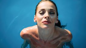 Exotic beautiful woman sunbathing and swimming royalty free stock photo