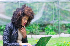 Exotic beautiful young girl using laptop in the Royalty Free Stock Image