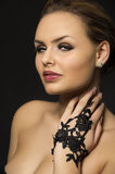 Exotic beauty. Closeup head and shoulders studio portrait of an exotic beauty with sultry eyes and bare shoulders posing with her hand in a black lace glove Stock Image
