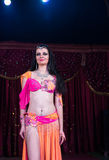 Exotic Belly Dancer Standing on Stage Smiling. Three Quarter Length Portrait of Exotic Dark Haired Belly Dancer Wearing Bright Costume Standing on Stage Smiling stock photography