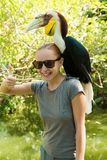 Exotic bird on a womans shoulder Stock Image