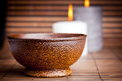 Exotic Bowl and Candles. An exotic Asian style wooden bowl on bamboo with candles Royalty Free Stock Photo