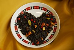 Exotic Chinese tea with buds of a clove, a coriander, slices of apples, oranges, pink pepper. Spicy black tea Cristmas cookies with buds of a clove, a coriander royalty free stock images